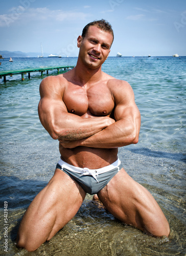 Handsome young bodybuilder in bathing suit kneeling