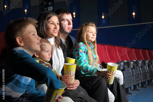 Friendly family with interest watching movie and eating popcorn