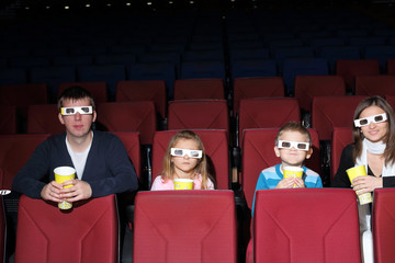 Parents with son and daughter in 3D glasses in the cinema
