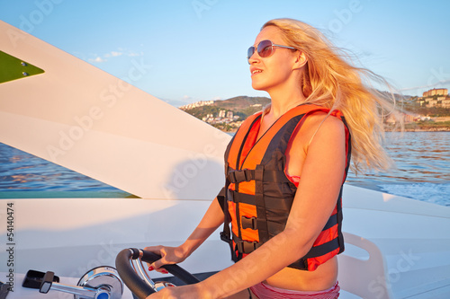 Woman in life-jacket  stands at helm of motorboat