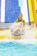 Boy shouts while slides down water-slide