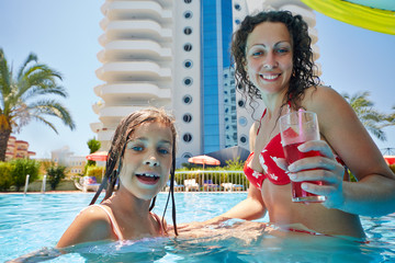 Mother with glass of beverage and daughter hide under umbrella