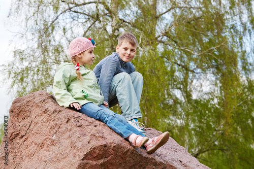 Boy and his younger sister sit on big block of granite