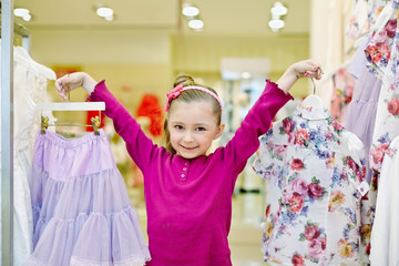 Joyfully smiling little girl shows hangers