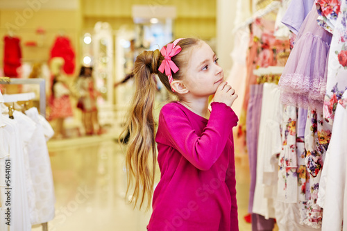 Little girl looks with interest, touching chin with fingers