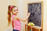 Half-length portrait of little girl who draws with chalk