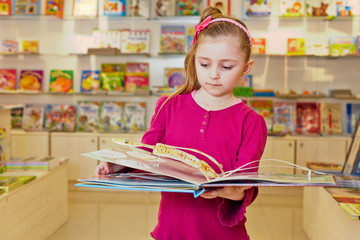 Little girl views fold-out book on anatomy in book department