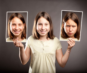 young girl holding two photos of herself