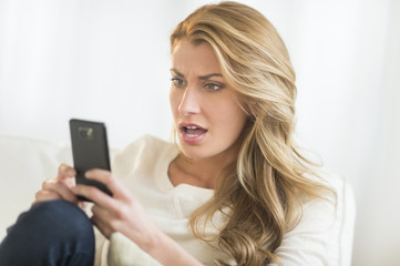 Amazed Woman Looking At Mobile Phone On Sofa