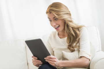 Woman Looking At Digital Tablet While Sitting On Sofa