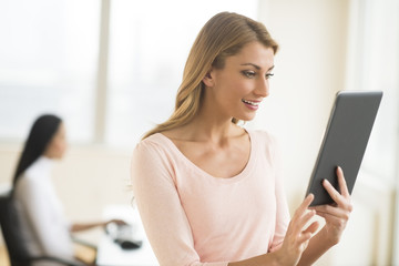 Happy Businesswoman Looking At Touchpad In Office