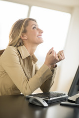 Happy Businesswoman Looking Up While Sitting At Desk