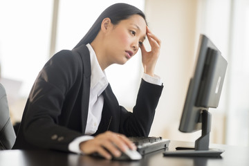 Overworked Businesswoman Working On Computer