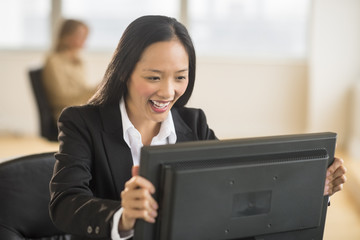 Happy Businesswoman Looking At Computer Monitor In Office