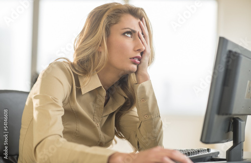 Frustrated Businesswoman Sitting At Computer Desk