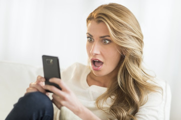 Shocked Woman Looking At Mobile Phone At Home
