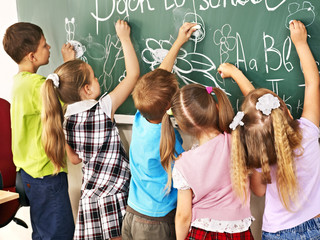 Children writing on blackboard.