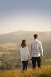 young couple look out over a beautiful landscape