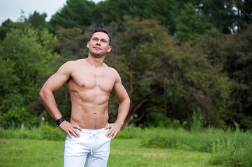 Man in white pants stands on the grass