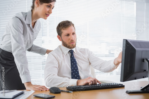 Businessman showing his colleague something on computer