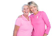 Mature women wearing pink tops and ribbons for breast cancer