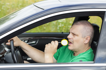 Man  in  car with yellow lollipop