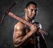Muscular man holding pickaxe