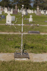 A metal cross with no words on it marks a grave.