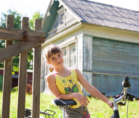 Girl with a bicycle against a village house