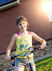 Girl on a bicycle against the brick wall at house