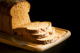 Brown sliced granary loaf on wooden chopping board
