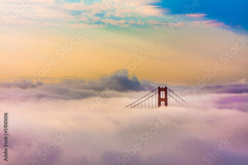 Fotobehang San Francisco World Famous Golden Gate Bridge in thich Fog after Sunrise