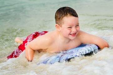 Child surfing on bodyboard at beach