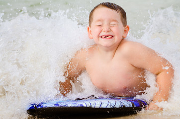 Child surfing on bodyboard at beach