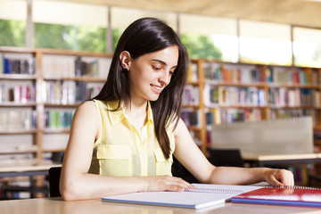Portrait of a female student with open book reading it in colleg