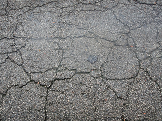 Old wet worn and cracked asphalt with cracks