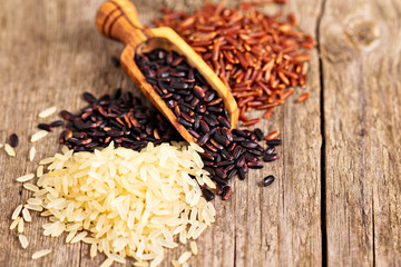 Variety of rice on a wooden background