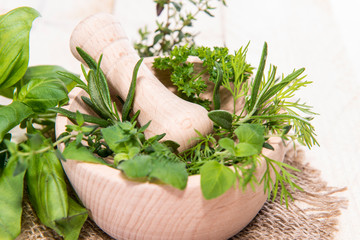 Fresh herbs in a small wooden bowl