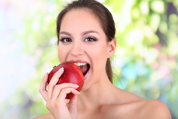 Young woman with apple on bright background