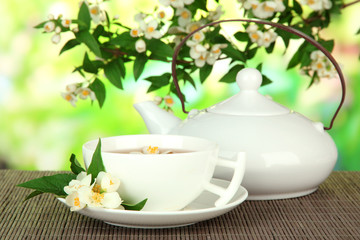 Cup of tea with jasmine, on bamboo mat, on bright background
