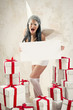 Woman as angel with heap of gift boxes holding empty white board