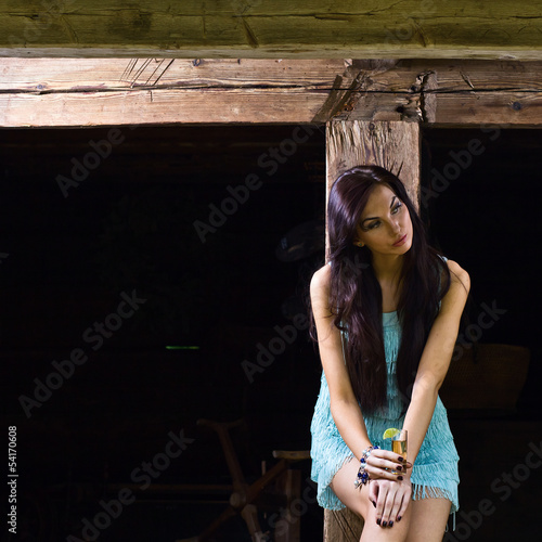 young beauty with tequila in the old wooden house