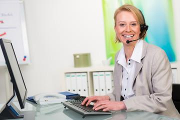 sekretärin mit headset am computer