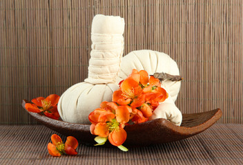 Herbal compress balls for spa treatment on bamboo background