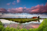 farmhouse and river at dramatic sunset