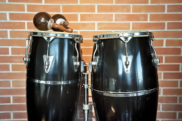 Congas and maracas in front of a brick wall