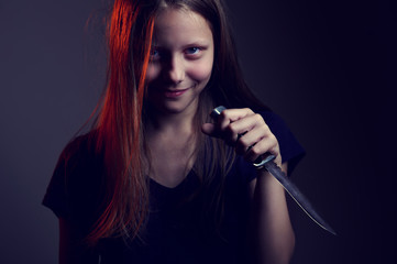 Portrait of a scary teen girl with a knife