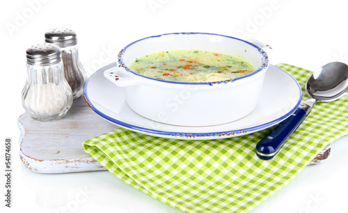 Soup in plate on napkin on wooden board isolated on white