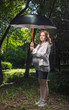 The pregnant woman costs in park under a umbrella