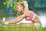 Fototapety An attractive female runner stretching before her workout